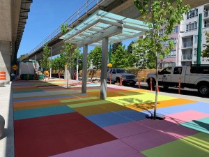 Image shows a sidewalk with colourful squares.