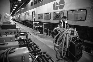 A worker carries cleaning tools next to a train.