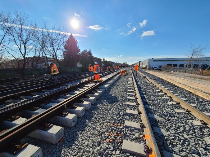 Workers install and inspect large sections of track