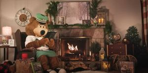 Image shows GO Bear reading a book next to a fire.
