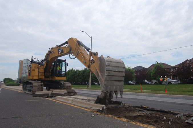 A tractor digs up a median.