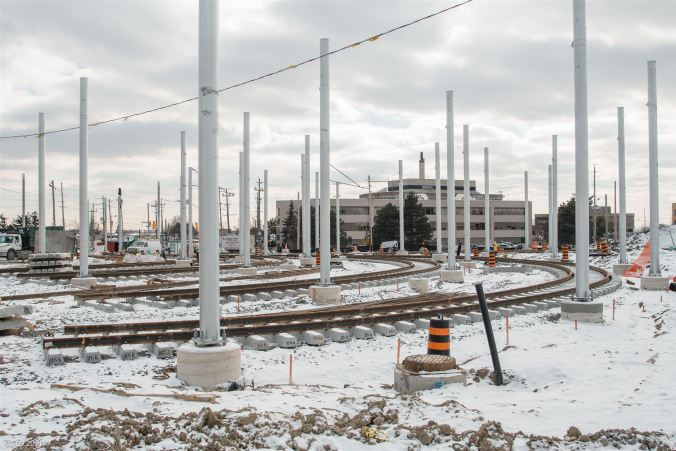 Track installation at ground level outside the Finch West LRT maintenance and storage facility.