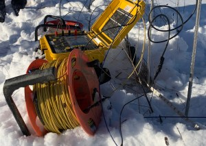 A small yellow block sits in the snow, attached to wires and posts stuck int the ground.
