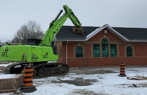 A tractor rips into the roof of a station building.