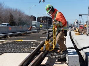 Image shows a worker working on rails.