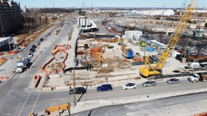 Image shows crews working at a site with a large crane.
