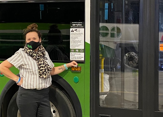 Image shows her standing by her bus.