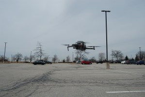 A drone takes off from a parking lot.