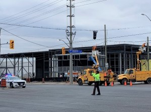 A Peel Regional Police officer patrols an intersection to ensure public safety near active construction sites. (Metrolinx photo)