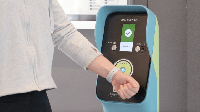 A person taps their smart watch on the UP Express terminal to pay.