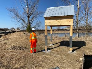 Image shows a Metrolinx staff member standing next to the bird house.
