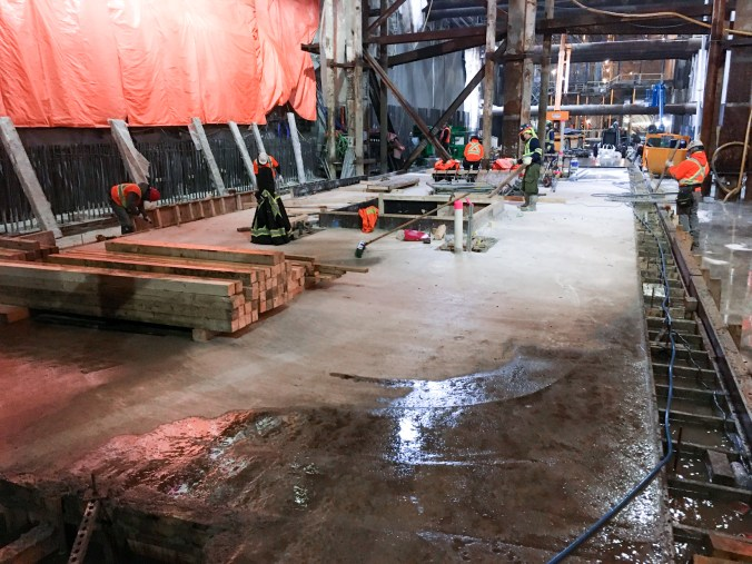 Image shows men working around newly poured concrete.