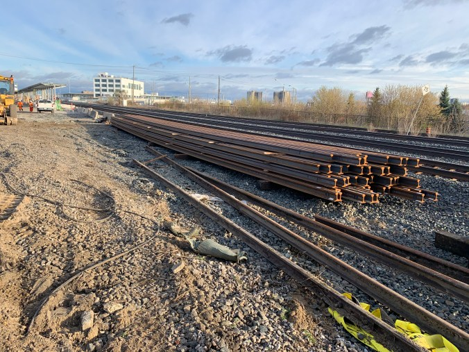 A pile of tracks rests beside a rail line.