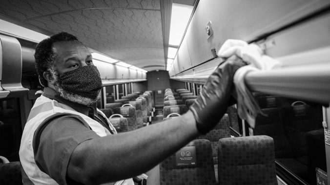 A worker scrubs the inside of a bus.