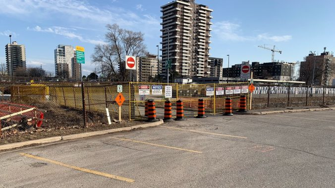 Construction fencing around a small creek in a parking lot at Port Credit GO