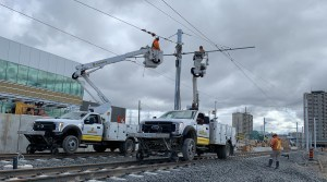 Image shows crews working in cherry-pickers above the tracks.