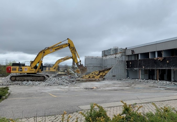 Image shows a large machine tearing away at a building.