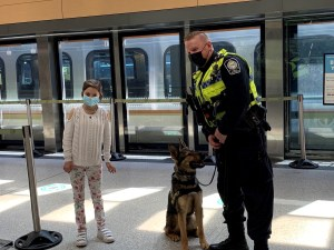 Romina stands next to a GO Transit Safety officer and his K9 partner at the UP Express terminal at Union Station.