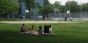 People have a picnic in a park as people play basketball nearby