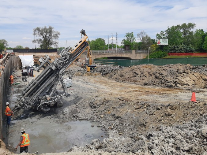 Image shows crews and machines working on the site.
