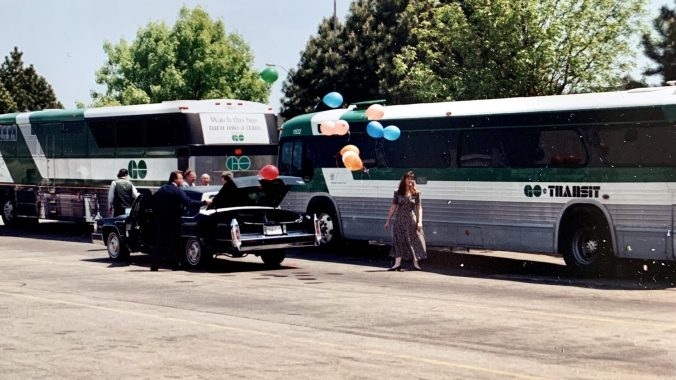 Vintage GO buses sit in the background as Fred Bentley's Cadillac makes a memorable entrance at his retirement party - balloons coming out of the trunk