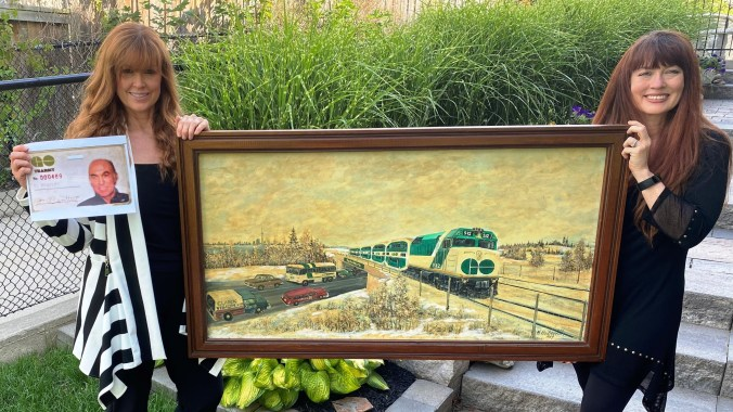 Fred Bentley's daughters Julie and Lisa hold the one-of-a-kind painting done by a local artist in 1989 – featuring an older model GO train and GO bus.