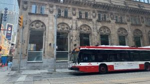 Image shows a bus going by a building in downtown Toronto.