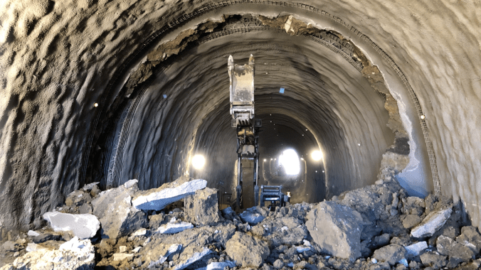 An excavator breaking through the end of tunnel one.