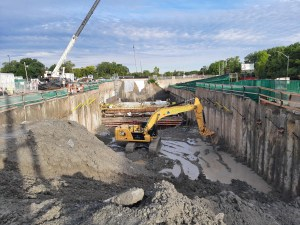 Image shows a muddy work site and large machinery.
