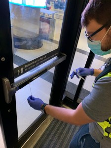 Image shows a person taking a sample from a door.