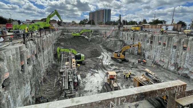 Excavators and other heavy machinery digging in a large excavation