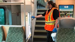 cleaning staff wiping down the inside of a GO Train