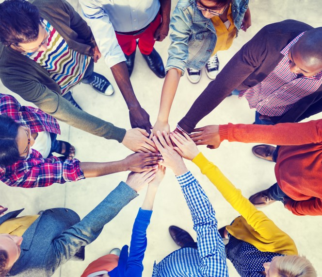 diverse group of people with their hands in a circle