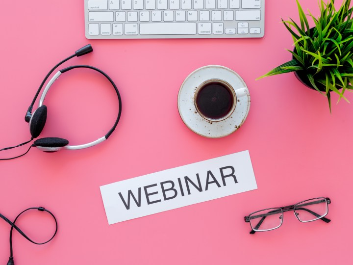 "laptop, coffee, headphones, glasses and succulent plant on a pink background with the word ""webinar"" on a strip of paper"