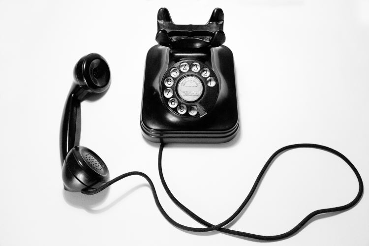 black rotary phone on a white background