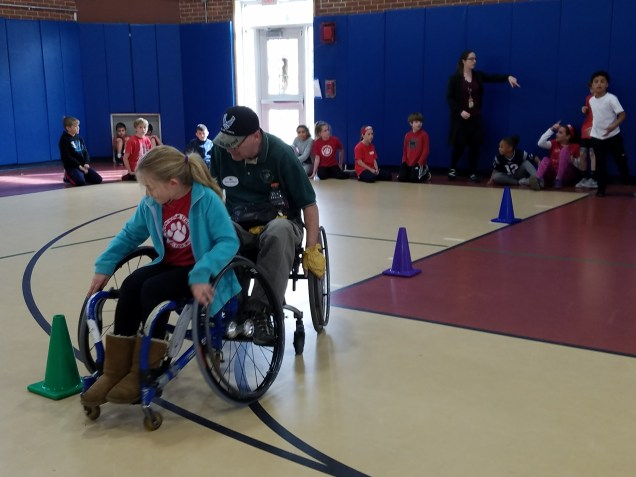 Cunningham 4th graders try out wheelchairs with volunteers from The Paralyzed Veterans of America.