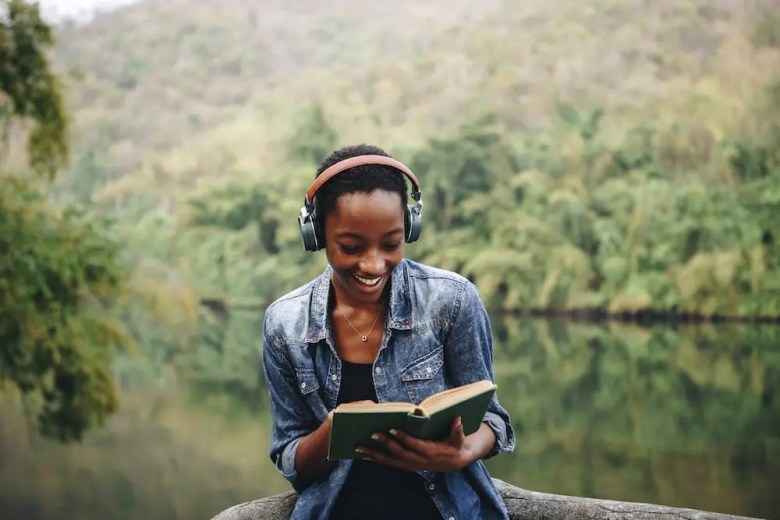 Woman listening to music while reading a book
