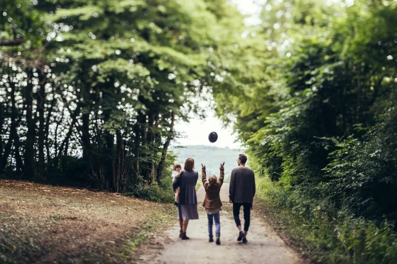 Family walking on a road in the forest