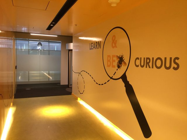 Leadership principles are everywhere at Amazon as depicted in this picture of a wall of the Vancouver Amazon Ofifice showing the Learn and Be Curious leadership principle.