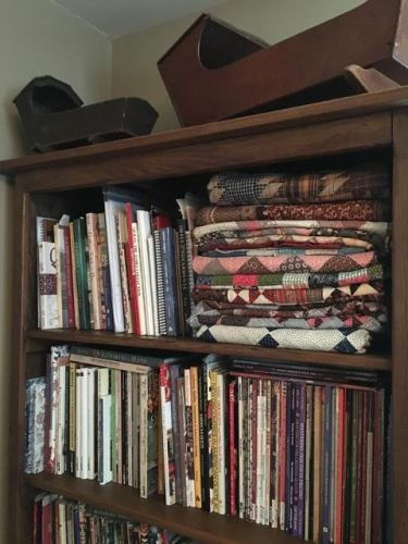 some antique quilts:tops folded on a bookshelf at the studio.