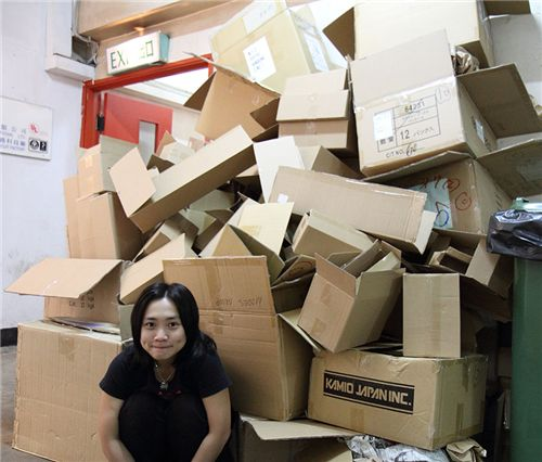 Lok in front of lots of empty boxes after a delivery from Japan