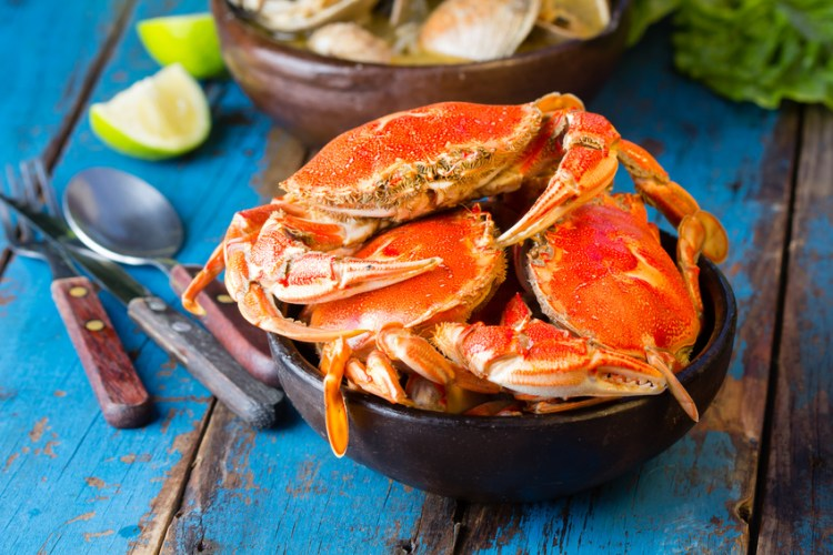 Seafood. Bowl of crabs and soup of slams on wooden blue background. Traditional food on Holy week Easter in Latin America.