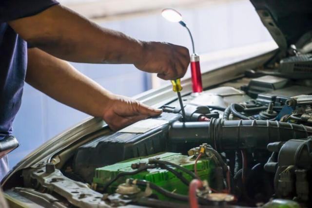 Carro com o capô aberto, recebendo manutenções por mãos masculinas que seguram uma chave de fenda, mecânico decidindo se há necessidade de trocar bateria.