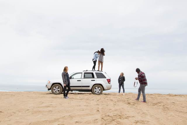 Grupo de amigos em uma praia, se divertindo ao redor de um carro, felizes pois encontraram o melhor preço de baterias