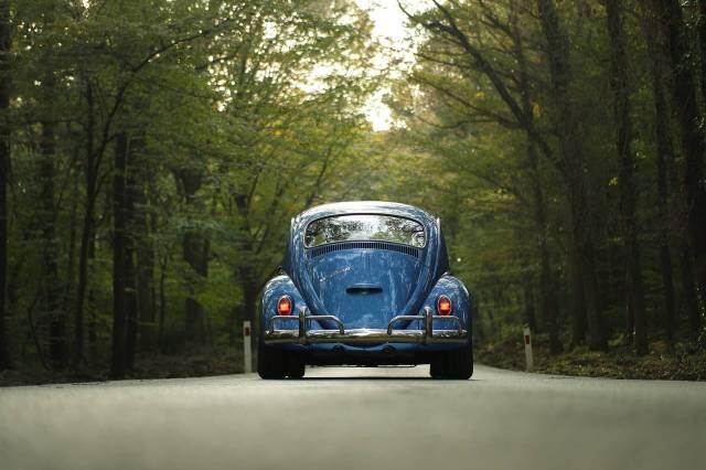 As costas de um carro azul enquanto ele dirige em uma estrada rodeada por florestas ilustrando como comprar bateria de carro