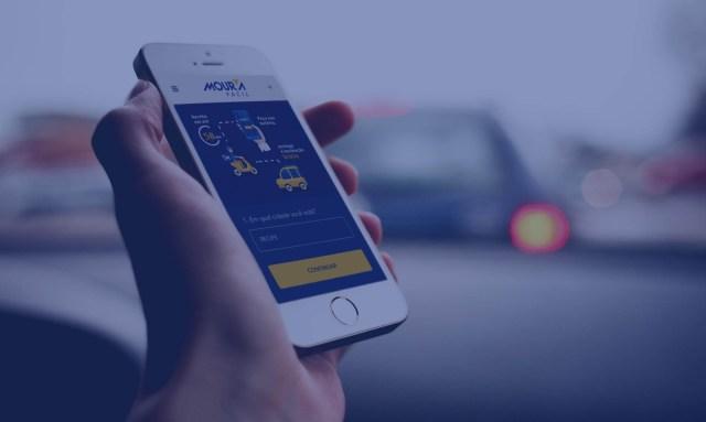 Mão segurando um smartphone branco, cuja tela mostra o site mourafacil.com, pessoa prestes a trocar bateria.