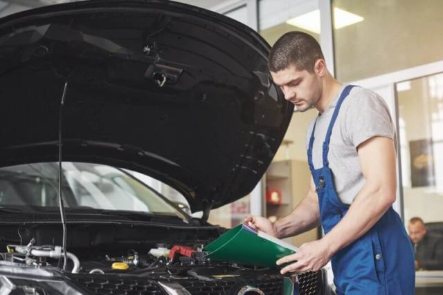 Na imagem um mecânico está realizando a troca do óleo do motor.