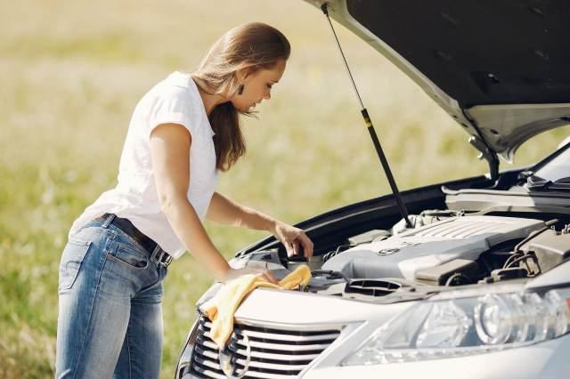 Na imagem, uma motorista está verificando os componentes em baixo do capô do carro, uma vez que a revisão é um procedimento para evitar que aconteça os estouros no coletor de admissão