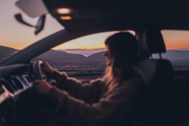 Imagem de uma motorista dirigindo um carro que a bateria não segura carga