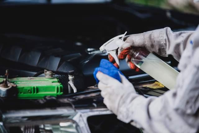 Imagem de mãos usando luvas e segurando um pano e um líquido para mostrar como lavar o carro debaixo do capô